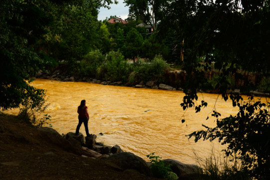 In this Denver Post photograph, Kalyn Green, resident of Durango, stands on the edge of the Animas River